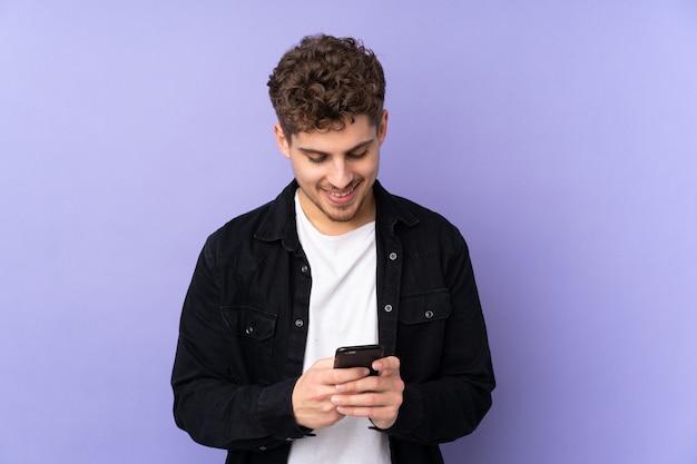 携帯電話でメッセージを送信する紫色の壁に白人男性