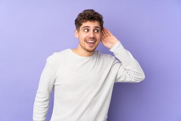 Кавказский человек на фиолетовой стене слушает что-то, положив руку на ухо
