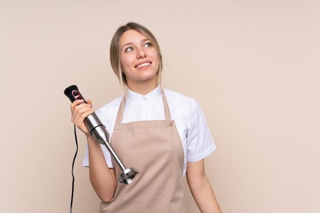 Молодая белокурая женщина используя ручной блендер смотря вверх пока усмехающся
