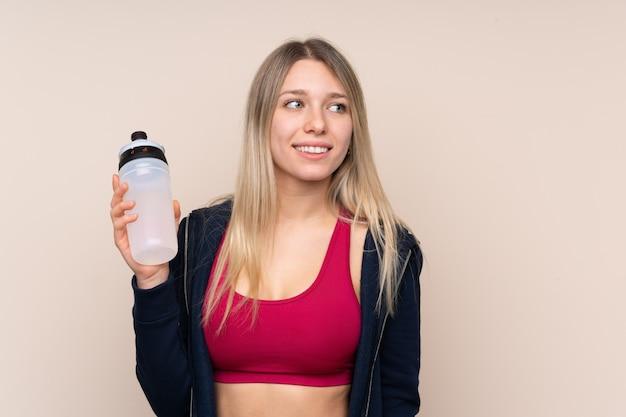 スポーツ水筒を持つ若いスポーツブロンドの女性