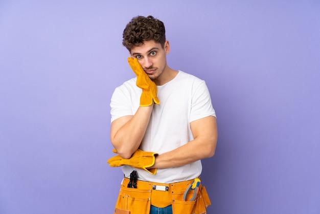 不幸でイライラした紫色の壁に若い電気技師男