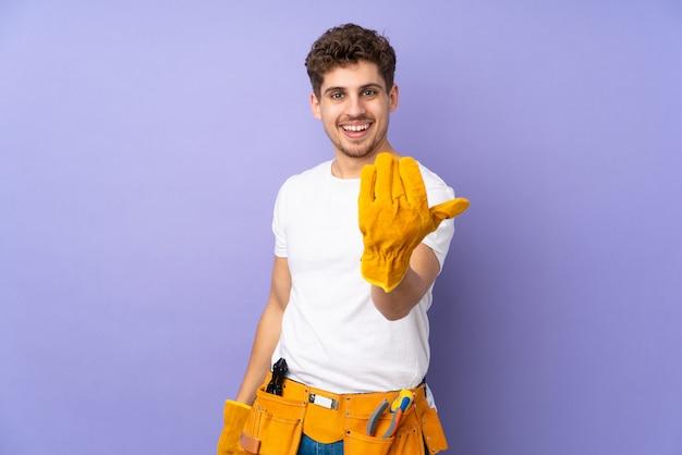 Молодой электрик человек на фиолетовую стену, приглашая прийти
