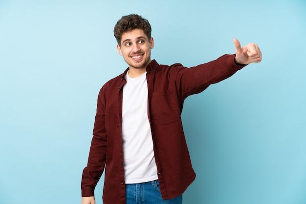 Молодой человек кавказской стены, давая пальцы вверх жест