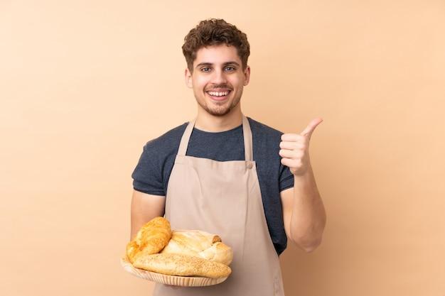Мужской пекарь держит стол с несколькими хлебов на бежевой стене, давая недурно жест