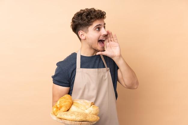 Мужской пекарь держит стол с несколькими хлебами на бежевой стене, крича с широко открытым ртом