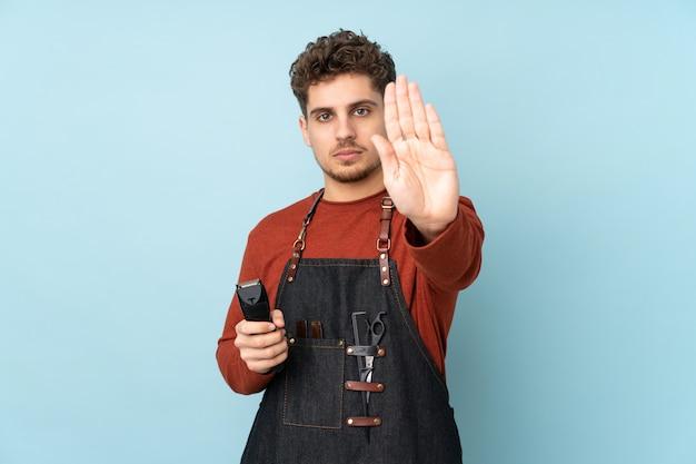 Парикмахер кавказских человек на синей стене, делая остановки жест рукой