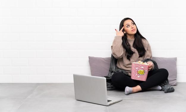 ポップコーンのボウルを押しながら頭に指を置いて狂気のジェスチャーを作るラップトップで映画を見せて若い女の子