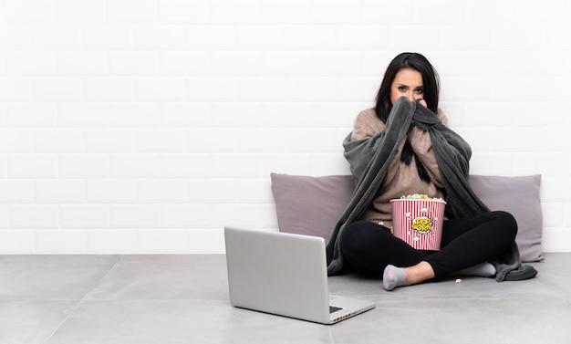 Молодая девушка держит миску попкорна и показывает фильм в ноутбуке замерзания