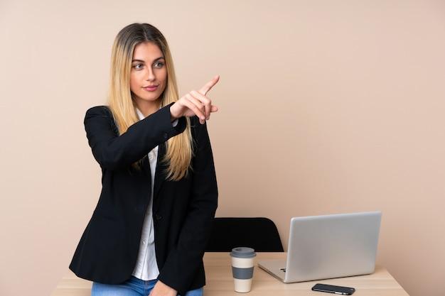 透明なスクリーンに触れるオフィスの若いビジネス女性