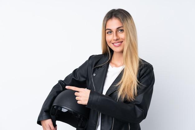 Молодая уругвайская женщина с мотоциклетным шлемом, указывая пальцем в сторону