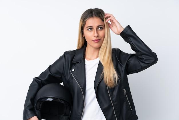 混乱する表情に疑問を持つオートバイヘルメットを持つ若いウルグアイ女性