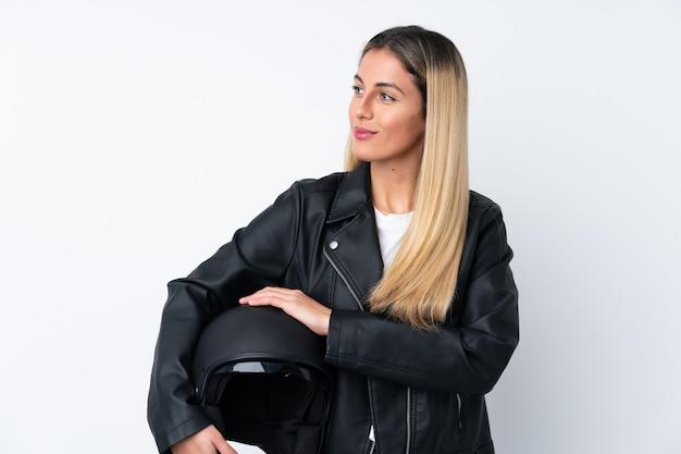 Молодая уругвайская женщина с мотоциклетным шлемом смотрит в сторону