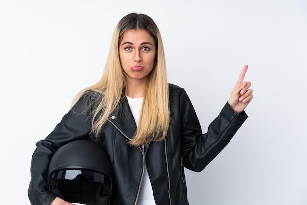 Молодая уругвайская женщина с мотоциклетным шлемом, указывая на боковые стороны, имеющие сомнения