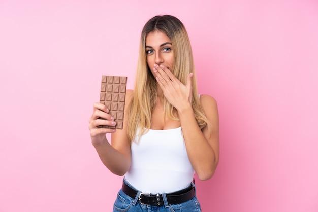 Молодая уругвайская женщина берет шоколадную таблетку и удивляется