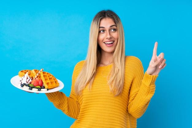 Молодая женщина, держащая вафли, намереваясь реализовать решение, поднимая палец вверх