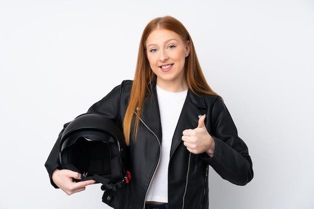 Рыжая молодая женщина с мотоциклетным шлемом с пальцами вверх, потому что случилось что-то хорошее