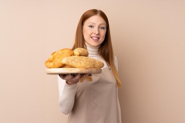 Женский пекарь держит стол с несколькими хлебов с счастливым выражением