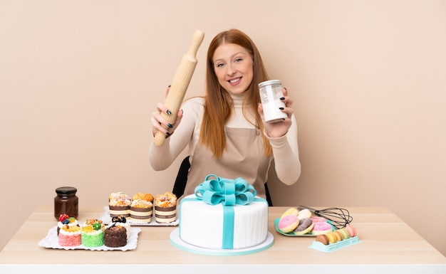 大きなケーキを持つ若い赤毛の女性