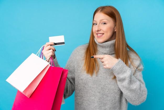 ショッピングバッグとクレジットカードを保持している若い赤毛の女性