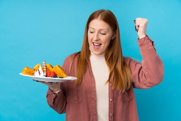 Молодая рыжая женщина, держащая вафли, празднует победу