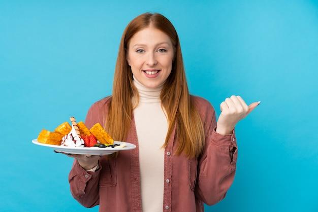 Рыжая молодая женщина, держащая вафли, указывая на сторону, чтобы представить продукт