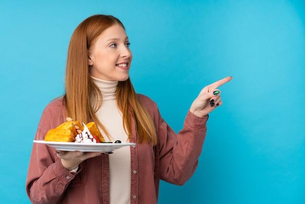 製品を提示する側を指しているワッフルを保持している若い赤毛の女性