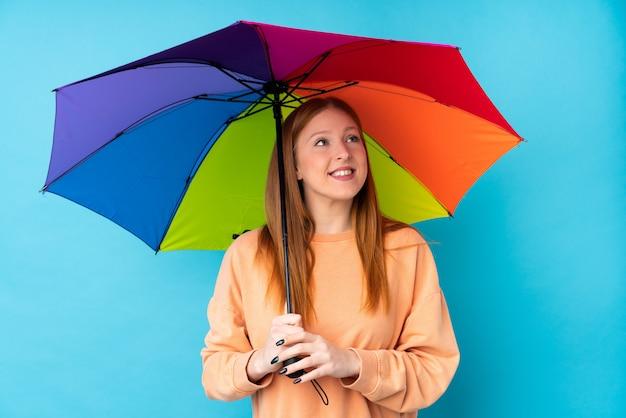 笑顔ながら見上げる孤立した壁に傘を保持している若い赤毛の女性