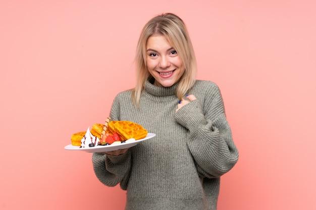Молодая белокурая женщина, держащая вафли с удивленным выражением лица