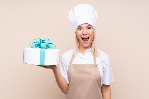 驚きとショックを受けた表情で大きなケーキを持つ若いロシア人女性