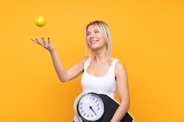 計量機とリンゴの若い金髪ロシア人女性