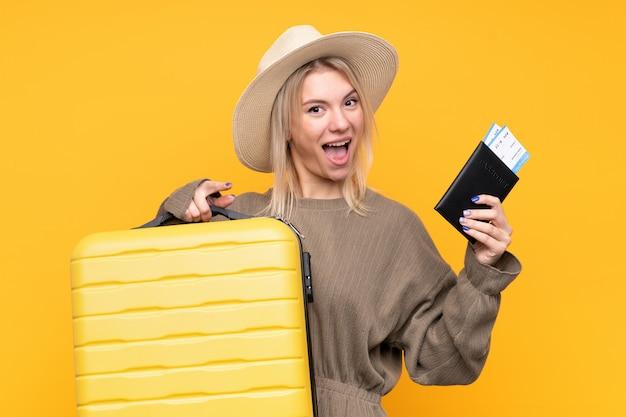スーツケースとパスポートと休暇で若いブロンドの女性と驚いた