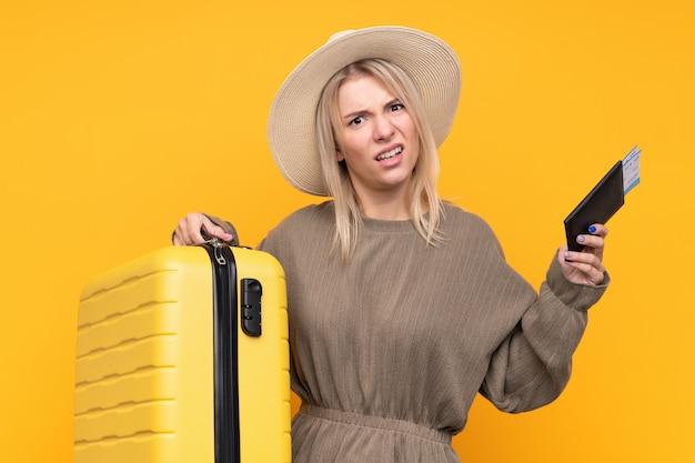 スーツケースとパスポートと休暇で不幸な若いブロンドの女性