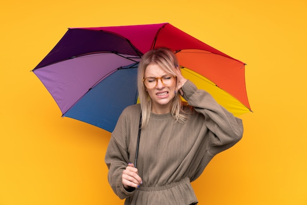 不満と何かに不満の傘を保持している若いブロンドの女性。負の表情