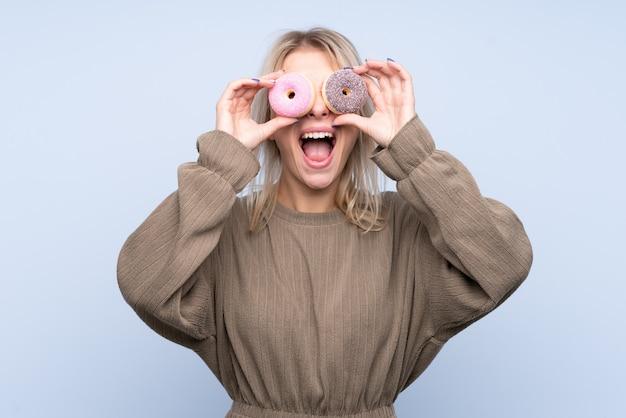 目にドーナツを保持している若いブロンドの女性