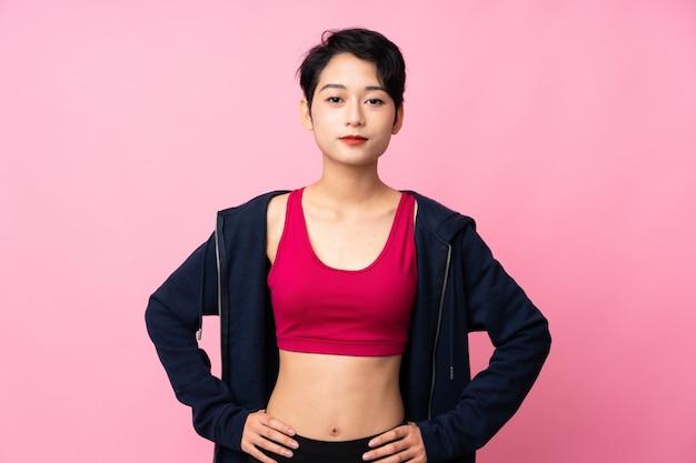 若いスポーツアジア女性が腰に腕を持つポーズ