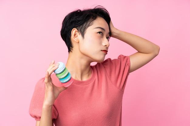 混乱した表情でカラフルなフランスのマカロンを保持している若いアジア女性