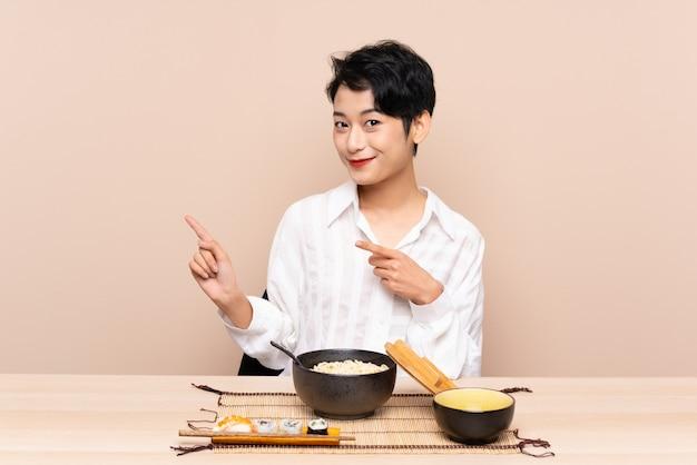 Молодая азиатская женщина в таблице с миской лапши и суши, указывая пальцем в сторону