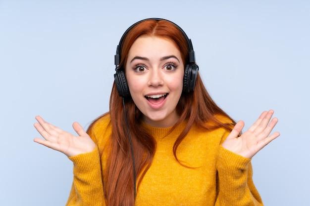 Рыжая девушка-подросток удивлена и слушает музыку