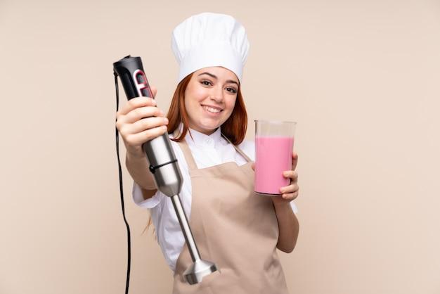 Рыжий подросток женщина, используя ручной блендер
