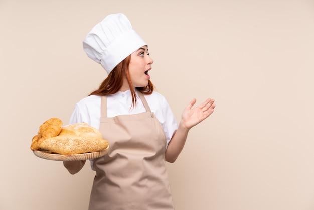 Женский пекарь держит стол с несколькими хлебцами с удивленным выражением лица