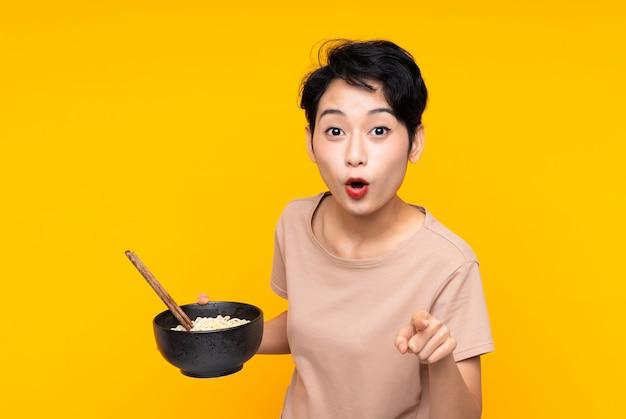 Молодая азиатская женщина удивила и указывая фронт пока держащ шар лапши с палочками для еды