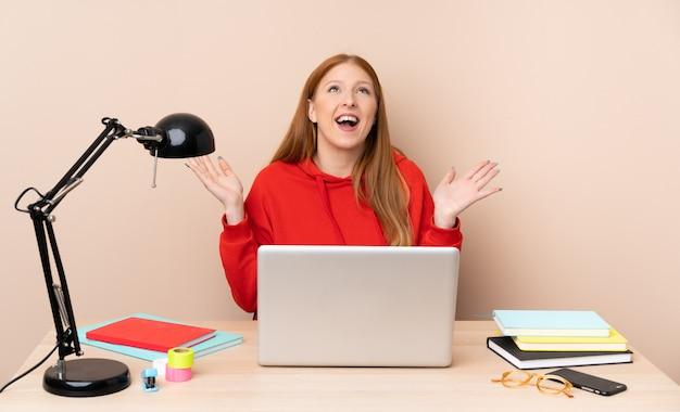 Молодой студент женщина на рабочем месте с ноутбуком много улыбается