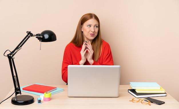 Молодой студент женщина на рабочем месте с ноутбуком интриги что-то