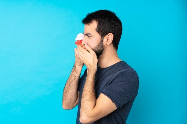口を覆っていると側にいる孤立した青い壁の上のコルネットアイスクリームと若い男