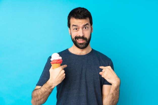 自分を指している分離の青い壁の上のコルネットアイスクリームと若い男
