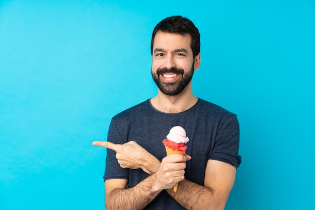 Молодой человек с мороженым корнет над синей стеной, указывая в сторону, чтобы представить продукт