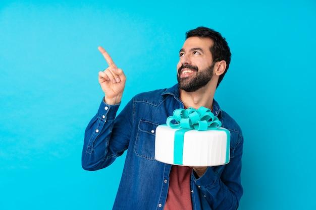人差し指で素晴らしいアイデアを指している分離の青い壁に大きなケーキを持つ若いハンサムな男