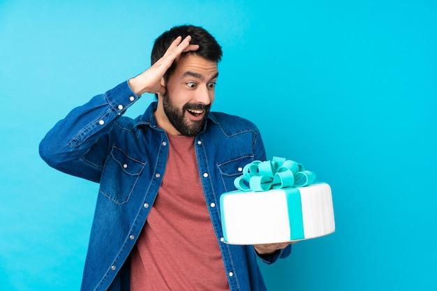 驚きの表情で孤立した青い壁に大きなケーキを持つ若いハンサムな男