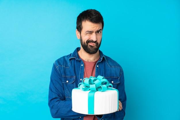 孤立した青い壁の気分を害する大きなケーキで若いハンサムな男