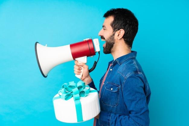 メガホンを通して叫んで分離の青い壁の上の大きなケーキで若いハンサムな男